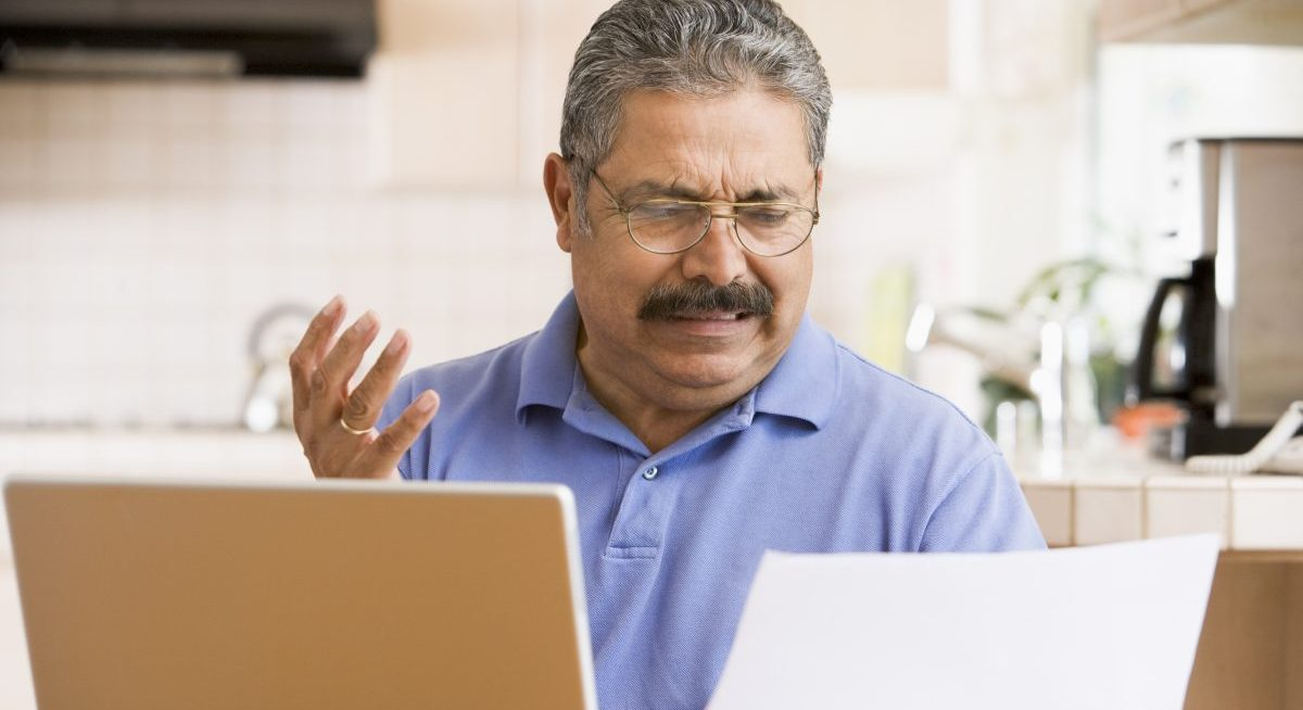 Image is of an older latino man sitting at his laptop with a piece of paper looking annoyed at it